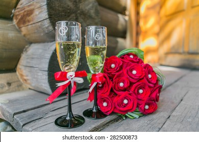 Wedding bouquete and glasses of champagne  on the wood