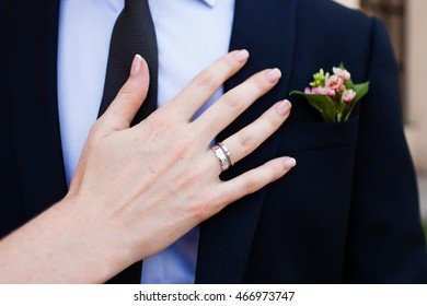Wedding boutonniere and the hand of bride with ring