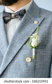 wedding boutonniere with natural flowers on a gray jacket