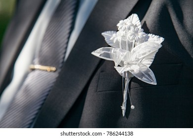 wedding boutonniere on suit of groom and tie