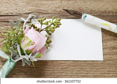 Wedding boutonniere with pink rose, pen and blank paper card on brown wooden table.
