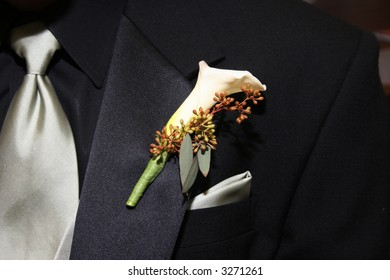 Wedding boutonniere pinned on the collar of a black wedding suit with silver tie and handkerchief