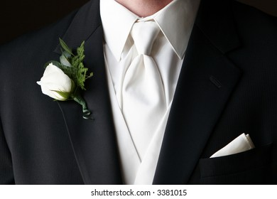 Wedding boutonniere pinned on the collar of a black wedding suit with white tie and handkerchief in pocket