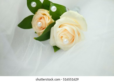 wedding boutonniere with rose and pearl on white fatin background, selective focus, place for text