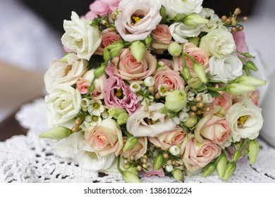 wedding bridal bouquet lies on the table with a lace napkin, next to it is a white teapot