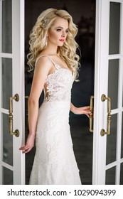 Wedding. Bride in a beautiful dress indoors in a white studio, like at home. The fashionable wedding style is taken in full length. Young attractive blond model with curly hair, like a bride