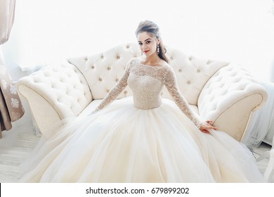 Wedding. Bride in beautiful dress sitting on sofa indoors in white studio interior like at home. Trendy wedding style. Young attractive caucasian brunette model like a bride