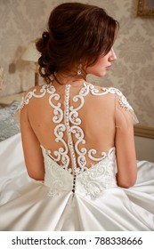 Wedding. Bride in beautiful dress sitting on sofa indoors in white studio interior like at home. Trendy wedding style .View back