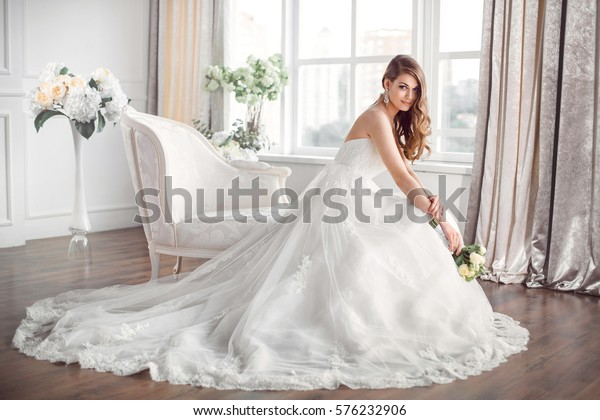 Wedding. Bride in beautiful dress sitting on sofa indoors in white studio interior like at home. Trendy wedding style shot in full length. Young attractive caucasian brunette model like a bride