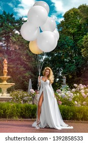 Wedding. Bride in a beautiful dress, standing in a beautiful garden and holding balloons. Trendy wedding style shot in full length. Young attractive caucasian blonde model like a bride - Image