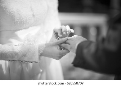 Wedding bride in bridal gown dress and groom in suit echanging coins in catholic christian marriage ceremony.