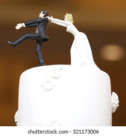 wedding bride and groom couple doll in funny action on wedding cake