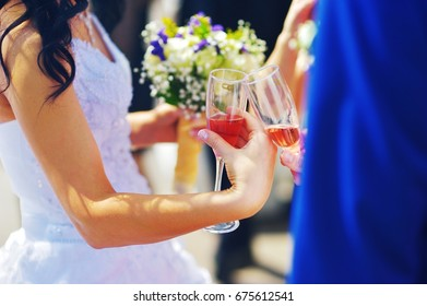 Wedding. The bride and groom are holding champagne glasses, close-up, without faces, partial blur. Beautiful wedding background.