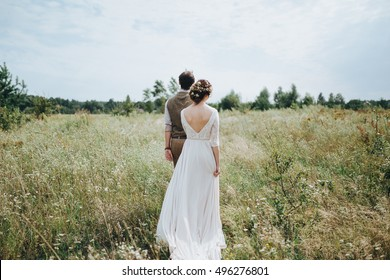 Wedding. Bride and groom holding hands and walk on the green field
