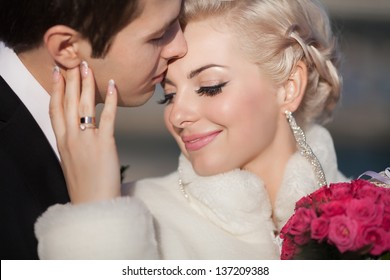 Wedding bride and groom kissing loving couple with roses bouquet flowers at winter bridal day Enjoy moment of happiness and having fun. playful newlywed family woman and man in love. gorgeous bride