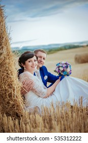 Wedding, bride and groom in nature in a haystack