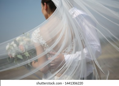 wedding bride and groom on top of a wind veil