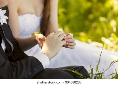 At the wedding, the bride putting on the ring on the groom's finger. Hand with rings . Outdoors