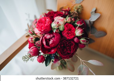 Wedding. The bride's bouquet. Wedding bouquet . A bouquet of red flowers, black berries and greens lying on a chair near the window