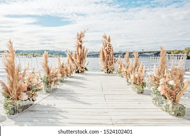 Wedding by the river. Beach wedding venue. Wooden stage with floral decorations arch