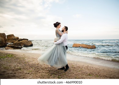 Wedding. Wedding by the sea. Young couple in love, bearded groom and bride in wedding dress at the seaside. Couple in love walking around the sea and the rocks near the place of the wedding ceremony.