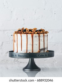 Wedding cake with blueberries, nuts and caramel on marble table