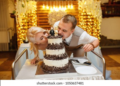 Wedding cake. Bride and groom bite cake. Crazy idea of cutting a wedding cake