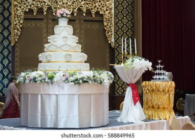 Wedding cake, candles and a glass of champagne for the bride and groom waiting for the wedding ceremony.