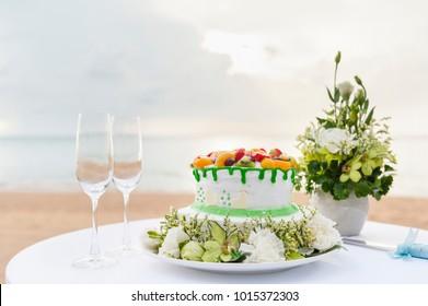 wedding cake and champagne wine glass on beach