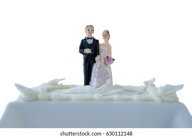 Wedding cake with couple figurines against white background