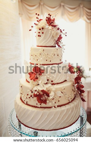 Wedding cake covered white icing red stock photo edit now wedding cake covered with white icing and red flowers mightylinksfo