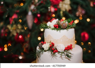 Wedding cake decorated with cones, pine, flowers and berries at winter reception on the background of Christmas tree