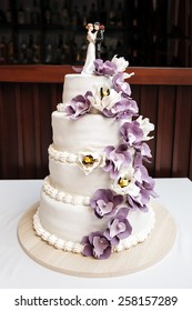 Wedding cake, decorated with purple flowers and figurines of bride and groom