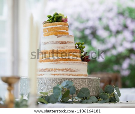 Wedding cake decorated for reception celebration. Layered cake is off center, falling sideways.