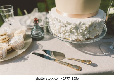 wedding cake with fondant cakes and macaroons on the table knife fork spatula and decor