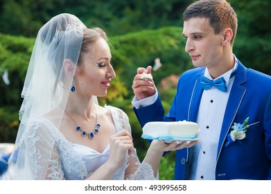 Wedding cake. The groom feeds the bride with wedding cake