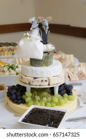 wedding cake made of cheese with buffet good in slightly blurred background. Cheese wedding cake has mice bride and groom for wedding topper.