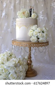 Wedding Cake on a gold and crystal stand with a vintage bride and groom cake topper and white roses