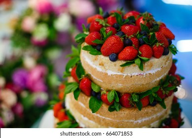 wedding cake with open biscuit shortcakes, cream and fruit. blueberries, strawberries, raspberries, red currants. Wedding cake, strawberry