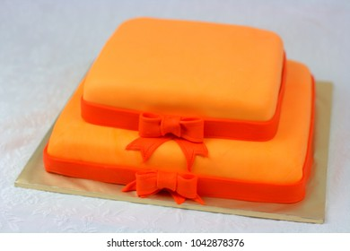 Wedding cake with orange color covered with fondant icing. square cake shaped with two tier cake.