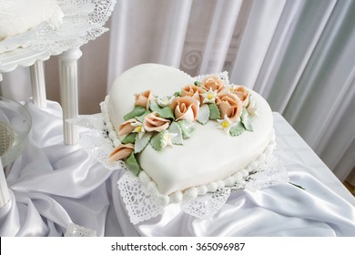 Wedding cake. Part of wedding cake in shape of heart, decorated with flowers
