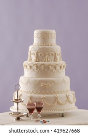wedding cake and red wine behind purple wallpaper