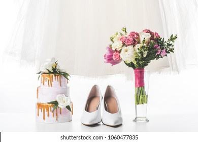 wedding cake with shoes, dress and bouquet isolated on white - Shutterstock ID 1060477835