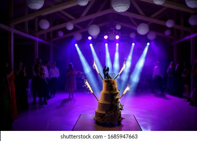 A wedding cake with silhouette of bride and groom with light show on the background