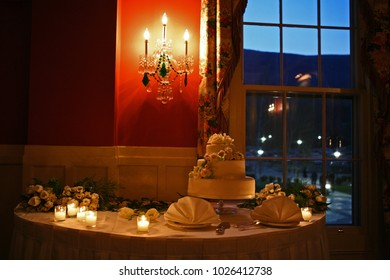 wedding cake surrounded with flowers on a table with candles