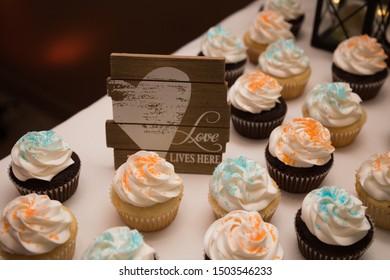 Wedding cake table decoration cupcakes chocolate vanilla white icing orange blue sign heart, love lives here, black lantern