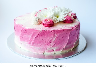 Wedding cake with white spring flowers and macaroon on top. Delicious pink cake