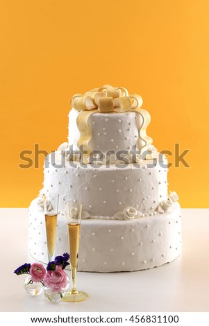 Wedding Cake With White Wine Glass Behind Orange Wallpaper