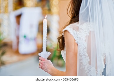 Wedding candle at hand of bride in church