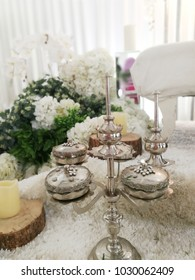 Wedding and candle on top of wooden decoration with white flower in background